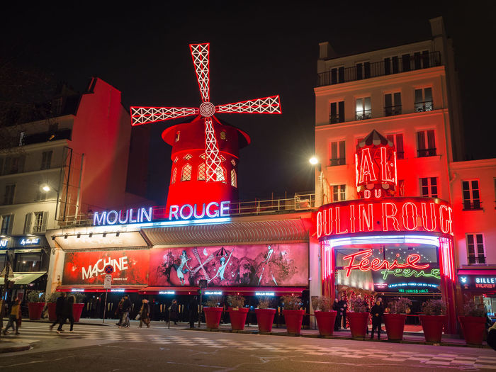 Montmartre, Paris - January 7, 2018: In Montmartre, among the most special places, there is certainly Place du Tertre. It 'a mix of street artists, portrait artists, painters, caricaturists. Moulin Rouge Paris By Night Cabaret Can Can Colors Dancers Entrance Entry Fun Illuminated Illuminated Signs Lights Montmartre Night Paris Red Shows For Adults Ticket Transgression Typical