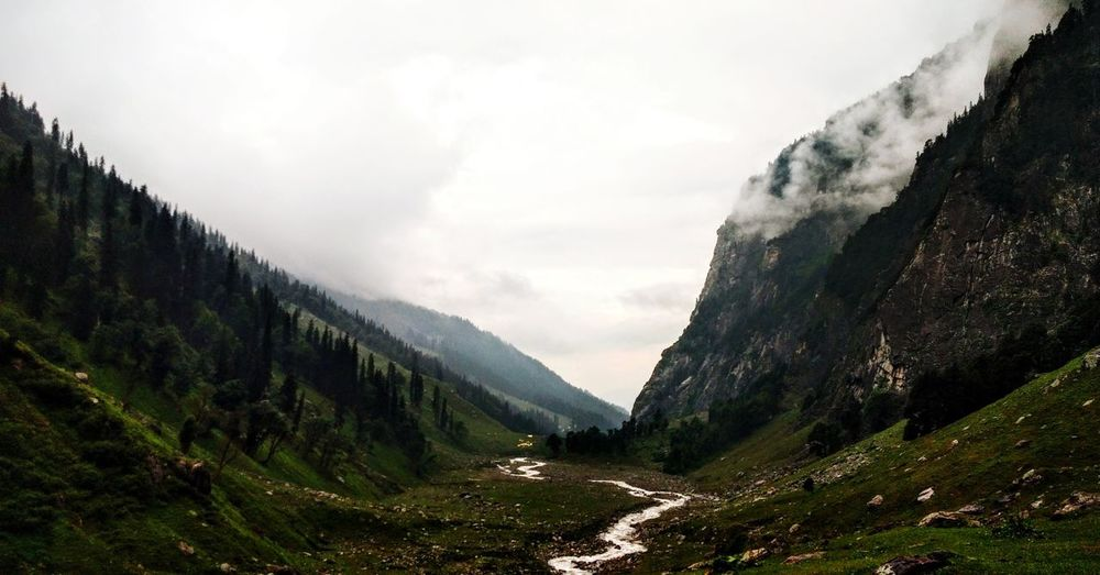 High angle view of stream amidst mountains against sky