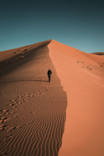 Rear view of man walking on sand in desert against clear sky