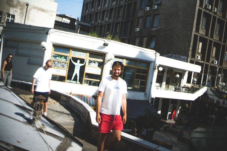 Full length of man standing on car in city