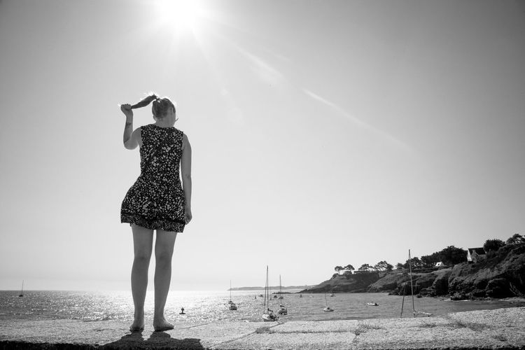 Rear view of woman standing on pier