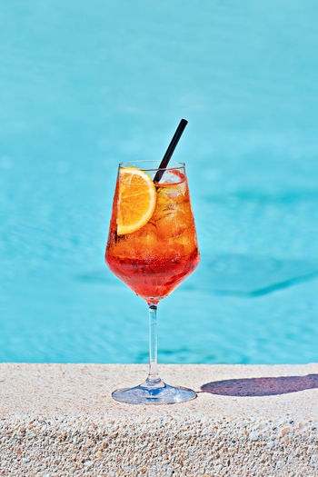 Wine glass of cold cocktail aperol spritz against turquoise water of poolside