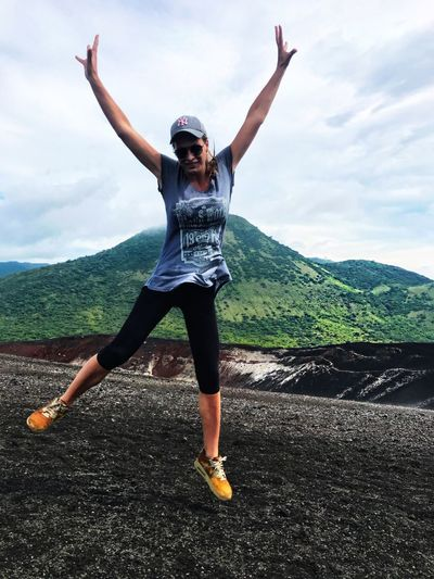 Sky Arms Raised Cloud - Sky One Person Full Length Arms Outstretched Mountain Front View Landscape Young Women Looking At Camera Nature Motion Jumping Happiness Joyful Adventure Volcano Volcanic Landscape Volcanoview Volcanic Landforms Lava Field Determination Volcanic Rock Energetic