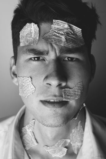 Close-Up Portrait Of Man With Newspaper Pieces On Face