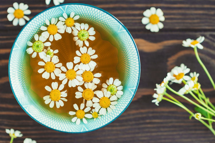 Directly above shot of herbal tea with flowers in cup on table