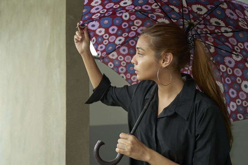 Young businesswoman  under umbrella while it is raining outdoors