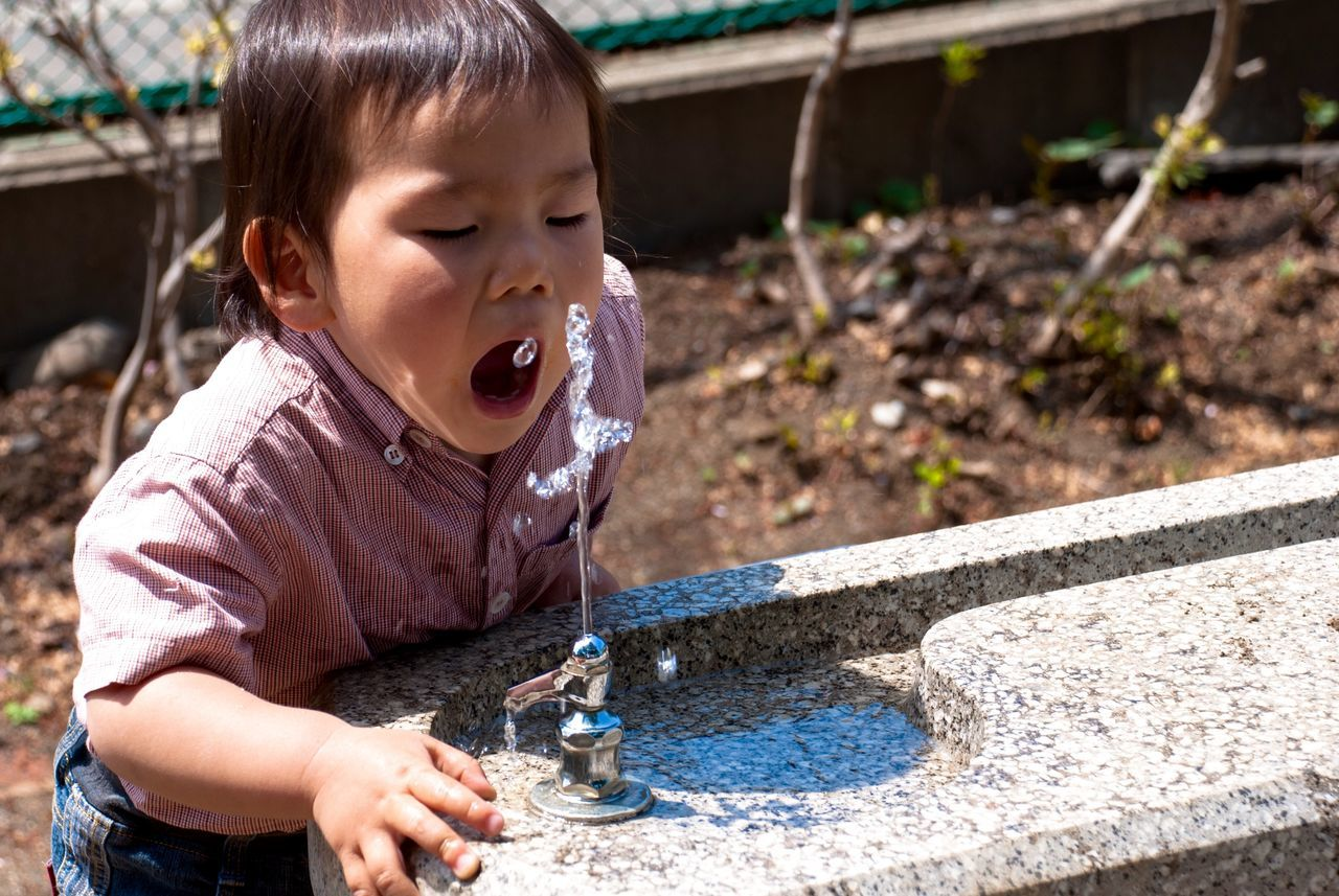 Boy drinking water from drinking fountain