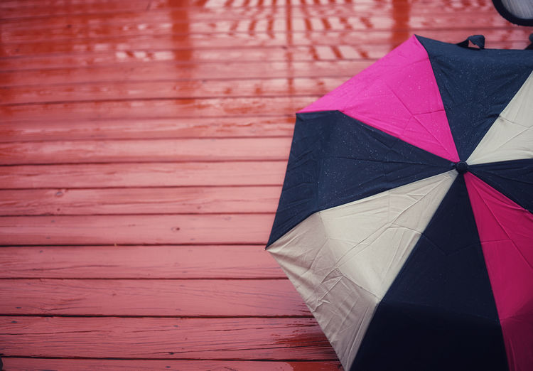 High angle view of pink umbrella on wooden deck