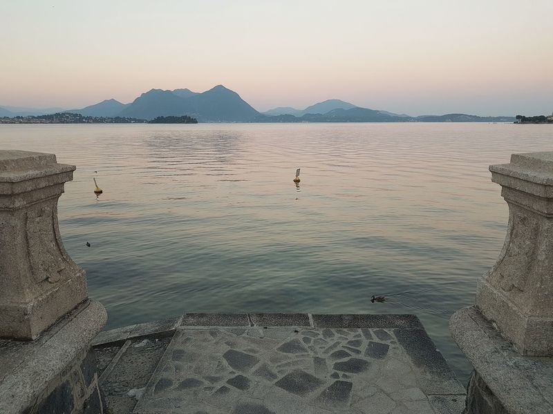 Scenic view of the Maggiore Lake from a terrace with coast in the background at sunset, Piedmont, Italy Coast Lake Lake View Piedmont Italy Baveno Maggiore Lake Sunset Sunset Lake Water Reflections Travel Vacation Lakescape Tranquility Serene Outdoors Beauty In Nature Italy Water Lake Sunset Mountain Dramatic Landscape Romantic Sky