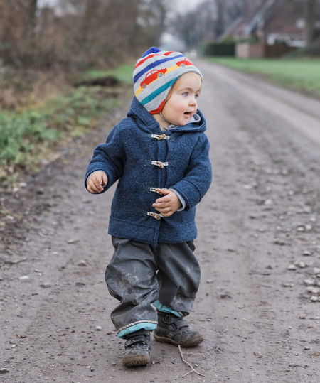 Toddler girl on footpath – Kempen, Germany Adventure Arm Baby Babyhood Bare Boot Building Casual Caucasian Cheerful Child Childhood Coat Curiosity Cute Dirt Duffle Coat Exploring Field Finger First Steps Footpath Front View Full Length Germany Gesturing Girl Hand Happy Hiking House Innocence Jacket Joy Messy Mud Nature One Outdoors Pants People Pointing Portrait Rural Standing Toddler  Tree Walking Wanderlust Winter One Person Males  Clothing Boys Casual Clothing Real People Day Focus On Foreground Looking Lifestyles Warm Clothing