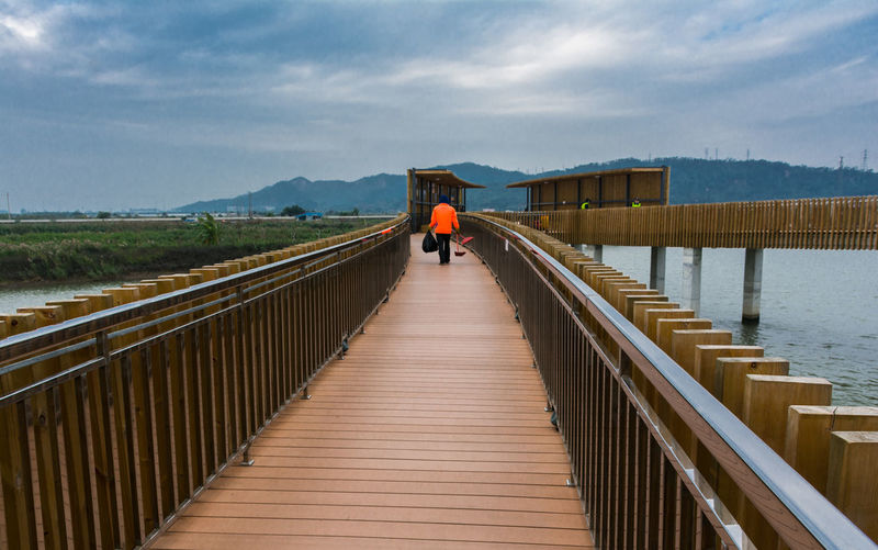 environmental sanitation worker Railing Architecture Sky Water Built Structure Cloud - Sky The Way Forward Bridge Connection Real People Direction Nature Lifestyles Day Rear View Scenics - Nature Bridge - Man Made Structure Adult People Outdoors Footbridge