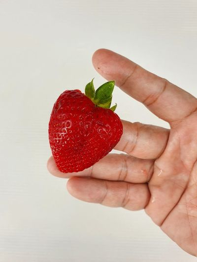 Cropped image of hand holding strawberry against white background