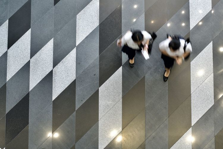 Directly above shot of women walking on flooring in office