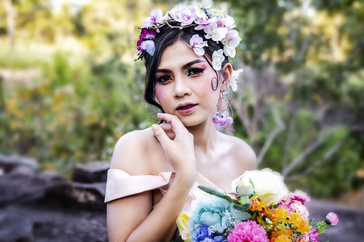 Portrait of beautiful bride with flowers at forest
