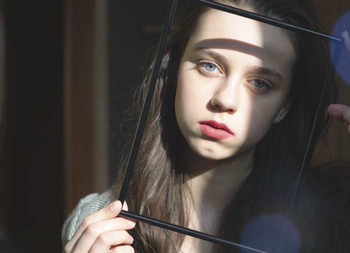 Close-up portrait of girl holding empty picture frame over face