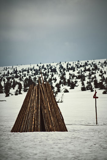 Wooden posts on snow covered land against sky