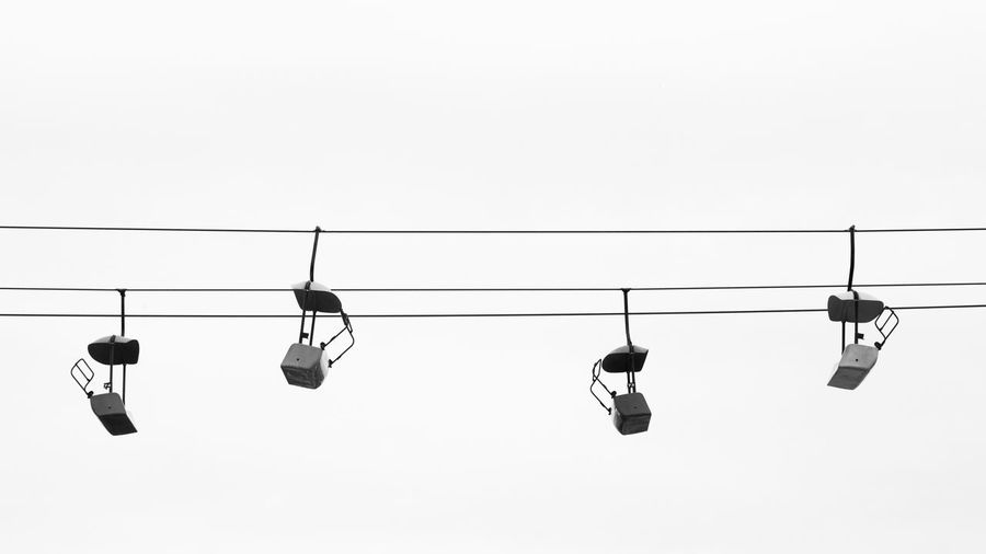 Low Angle View Of Overhead Cable Cars Hanging Against Clear Sky