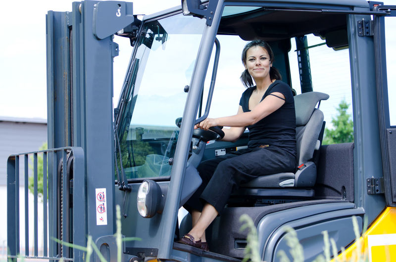 Portrait of happy woman sitting in forklift truck