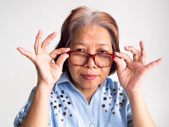 Portrait Of Senior Woman Wearing Eyeglasses Against White Background