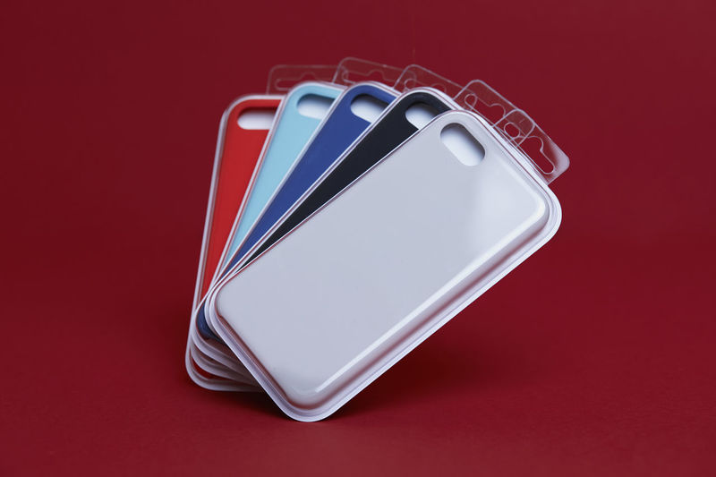 Set of Coloured Silicone Covers Cases for Smart Phone on a Red Background Red Colored Background Red Background Studio Shot Indoors  Metal No People Close-up Connection Still Life Technology Communication Copy Space Smart Phone High Angle View Wireless Technology White Color Single Object Office Supply Mobile Phone Silver Colored Personal Accessory