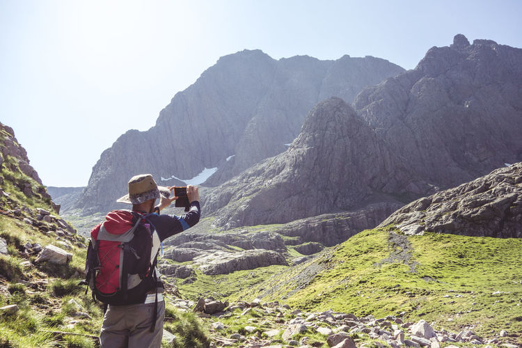 Rear view of hiker with backpack photographing mountains while standing on field