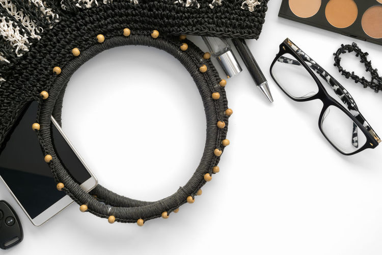 Women's handbag and accessories on a white background. Glasses Woman Bead Black Color Blank Bracelet Close-up Directly Above Fashion Flatlay Glasses Handbag  Headphones High Angle View Indoors  Listening Necklace No People Personal Accessory Still Life Studio Shot Table Tablecloth Technology White Background