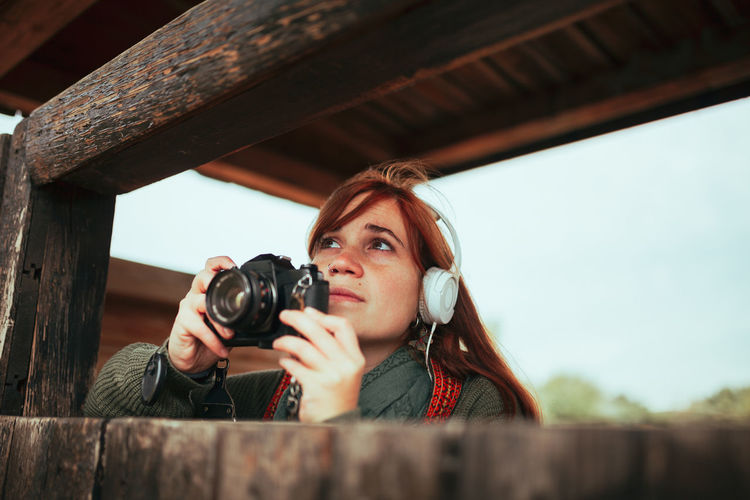 Close-up of woman looking away while photographing outdoors
