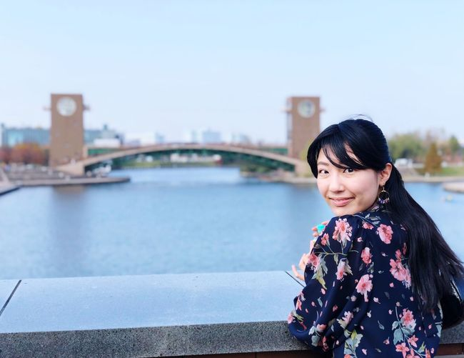 Portrait of woman standing against river in city