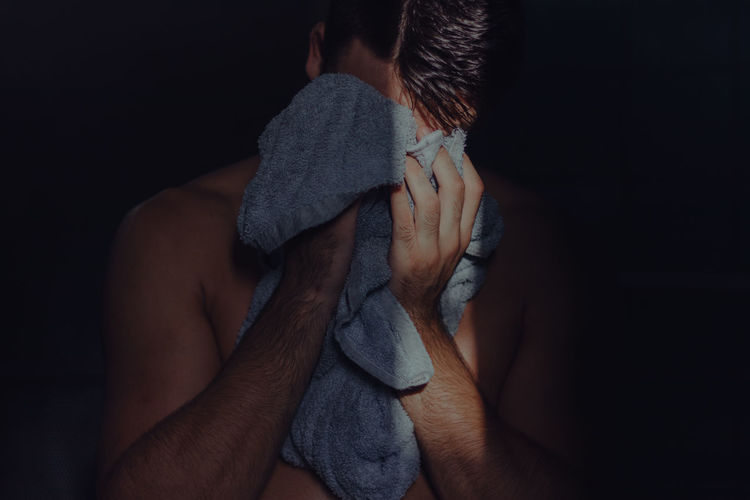 Shirtless Man Covering Face With Towel While Standing In Darkroom