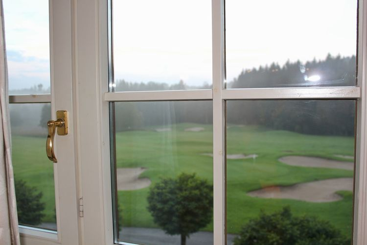 Scenic view of field seen through glass window