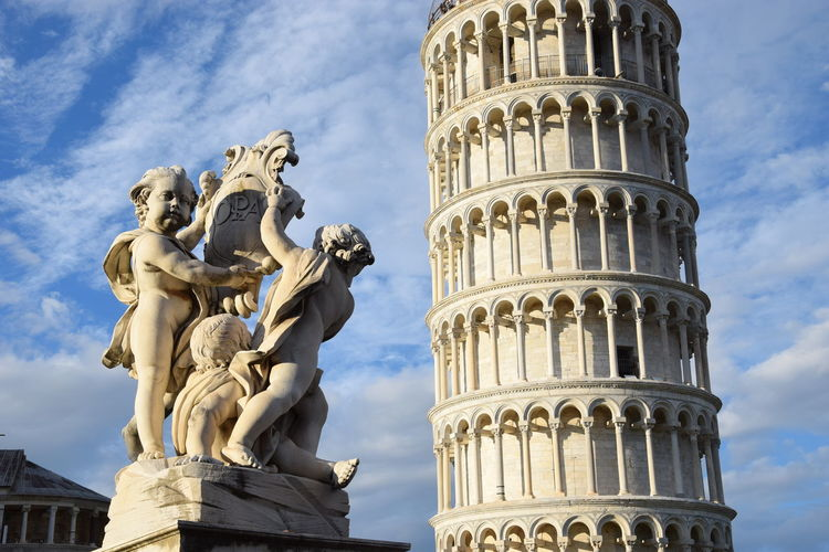 Statue and leaning tower of pisa against sky