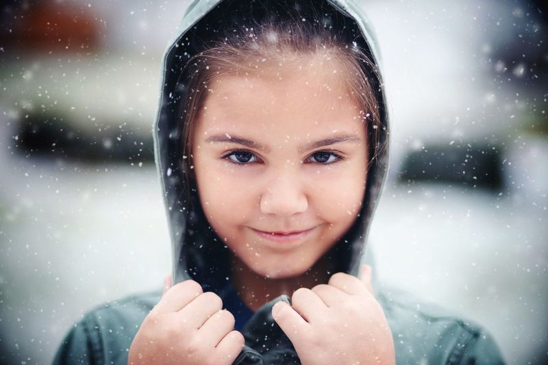 Portrait of smiling girl during snowfall