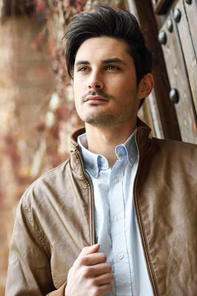 Portrait of a young handsome man, model of fashion, with modern hairstyle in urban background, wearing casual clothes. Beard Casual Clothing Clothing Contemplation Day Focus On Foreground Front View Fully Unbuttoned Jacket Leather Leisure Activity Lifestyles Looking One Person Outdoors Portrait Real People Standing Waist Up Young Adult Young Men