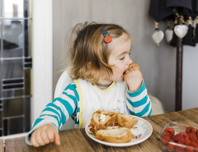 Cute girl eating bread while sitting by table at home