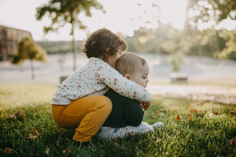 Side view of girl embracing brother