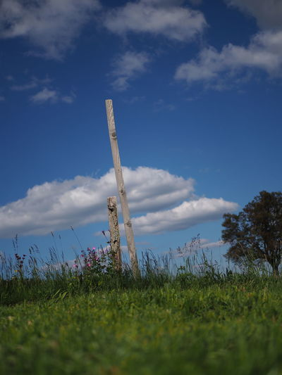 Low angle view of wooden post on field against sky