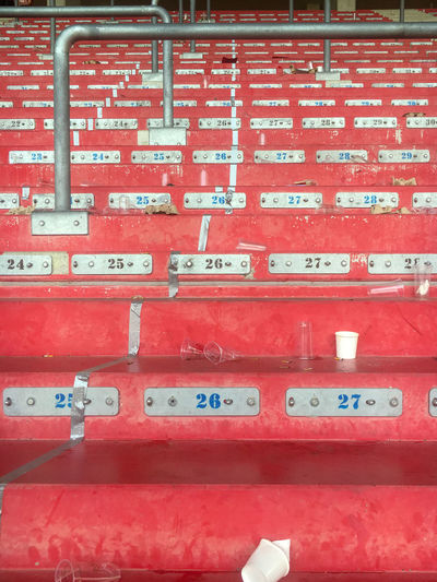 Empty red painted stand in a sports stadium with some rubbish after a match Red Text No People Full Frame Communication Indoors  Western Script Number Close-up Built Structure Container Backgrounds Wall - Building Feature Architecture Business In A Row Day Guidance Order STAND Stadion Stadium Arena Sports Empty Rubbish Waste Stands Venue