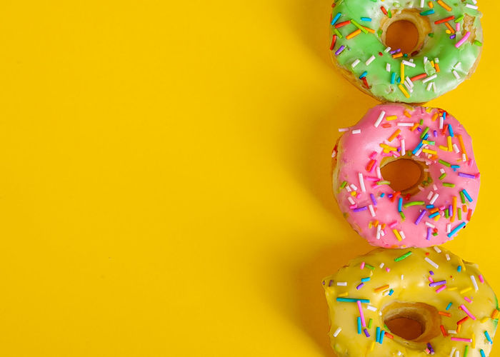 Close-up of multi colored candies against yellow background