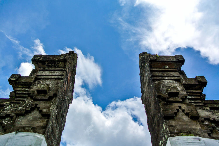 Low angle view of columns against cloudy sky at tanah lot on sunny day