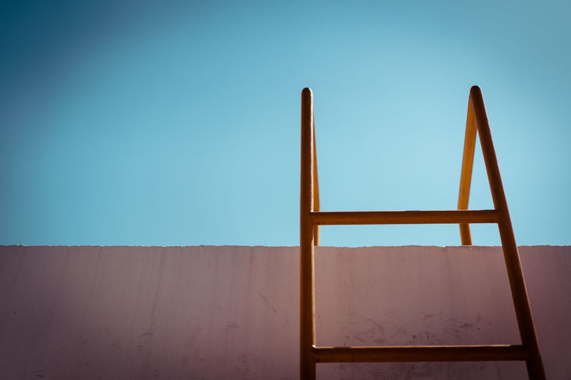 yellow metal ladder and stained wall in daylight, obstacle and success concept Blue Bright Climb Cross Day Emergency Escape Exit Fence Fight High Ladder Light Metal Obstacle Out Safe Safety Security Sky Stained Success Sunlight Wall Way Yellow