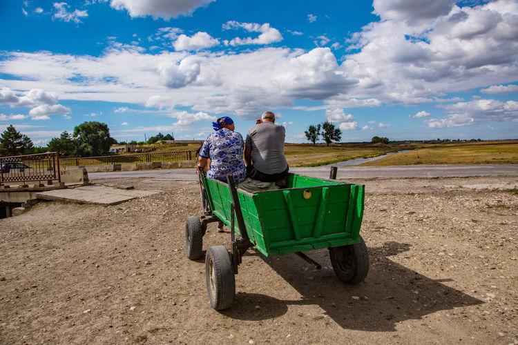 People sitting in cart on field against sky
