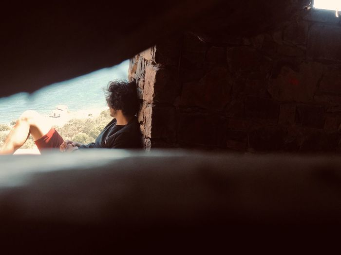 Young man seen through hole looking away while sitting against brick wall