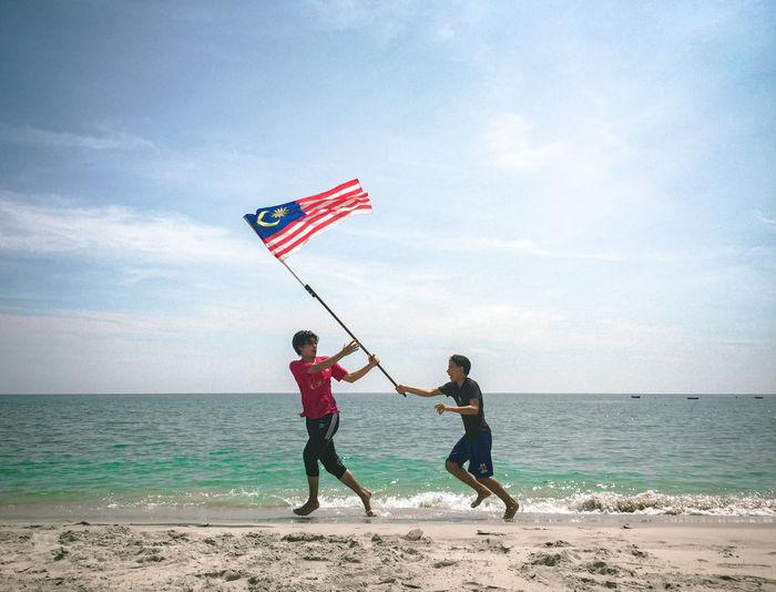 Men running with flag on beach against sky