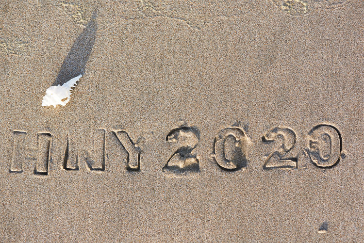 Happy new year 2020. A white seashell and imprinted texts and alphabets on the beach New Year Happy Seashell White Sand Beach Background Text Holiday Nature Design Concept Summer Texture Travel Sea Vacation Celebrate Word Type Celebration Good Light Fun Sign Season  Ocean Tropical Letter Number Font Date Seaside Wave Hello Calendar Sunlight Shadow Print
