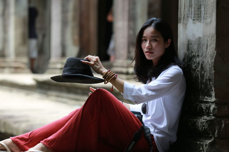 Portrait Of Young Woman Holding Hat Sitting By Architectural Column At Angkor Wat