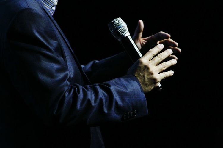 Midsection Of Businessman Holding Microphone While Standing Against Black Background