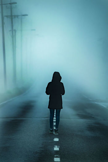 Rear View Of Woman Standing On Road During Foggy Weather At Night