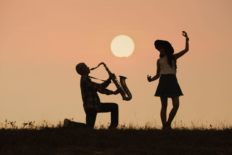 musician play saxophone with sunset or sunrise background Sunset Sky Orange Color Lifestyles Land Standing Two People Real People Nature Women Leisure Activity Togetherness Field Silhouette People Adult Girls Sun Outdoors Human Arm Arms Raised Music Dance Saxophone Couple