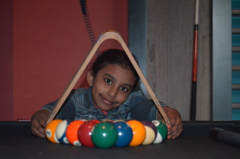 Portrait of girl holding cue balls at table