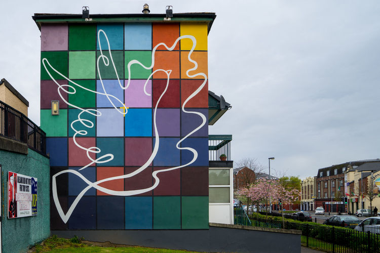 Architecture Building Exterior Built Structure Communication Day Derry Graffiti Ireland Irish Londonderry Multi Colored Mural Art Murales No People Northern Ireland Outdoors Road Sign Sky Text Tree Wallart